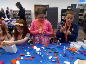 Kids making cool stuff at a blue table