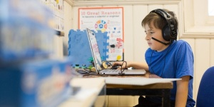 A child working on a laptop using headset microphone