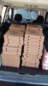 The back of a car loaded top to bottom with pizza boxes