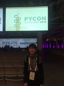 A photo of Joshua Lowe stood in front of the PyCon 1028 sign in Cleaveland, Ohio