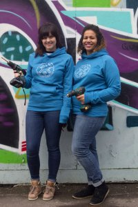 A photo of Ruth and Kisha stood against a wall holding drills